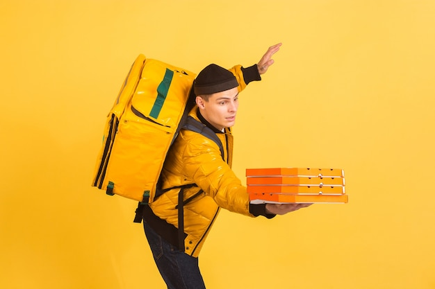 Servicio de entrega sin contacto durante la cuarentena el hombre entrega alimentos y bolsas de compras durante las emociones de aislamiento del repartidor aislado en la pared amarilla