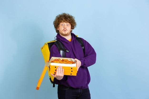 Servicio de entrega sin contacto durante la cuarentena, el hombre entrega alimentos y bolsas de compras durante las emociones de aislamiento del repartidor aislado en la pared azul