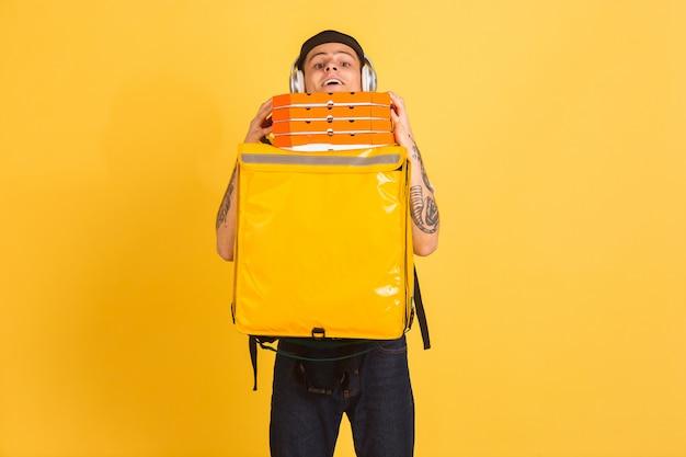 Servicio de entrega sin contacto durante la cuarentena. el hombre entrega comida y bolsas de compras durante el aislamiento. emociones del repartidor aislado en amarillo