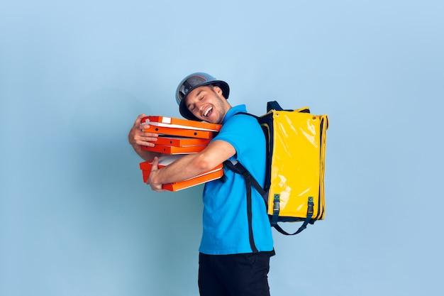 Servicio de entrega sin contacto durante la cuarentena. el hombre entrega comida y bolsas de compras durante el aislamiento. emociones del repartidor aislado en azul