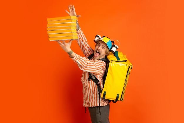 Servicio de entrega sin contacto durante la cuarentena. el hombre entrega comida y bolsas de compras durante el aislamiento. emociones del repartidor aislado en naranja