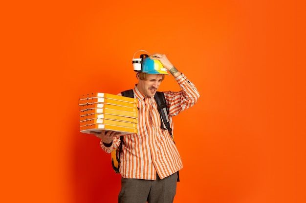 Servicio de entrega sin contacto durante la cuarentena. el hombre entrega comida y bolsas de compras durante el aislamiento. emociones del repartidor aislado sobre fondo naranja.