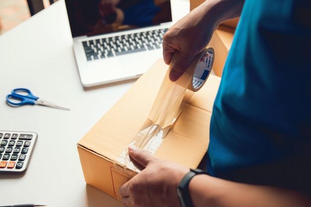Servicio de entrega de hombre trabajador y caja de embalaje de trabajo, propietario del negocio trabajando para verificar la orden antes de enviar al cliente por correo, envío de ventas en línea