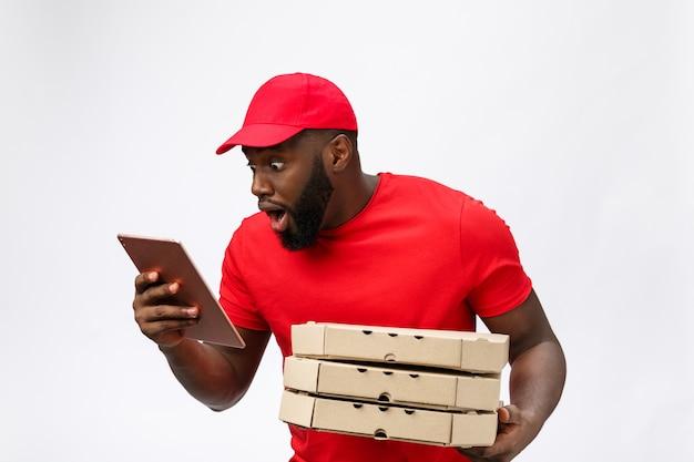Servicio de entrega: repartidor de pizzas africano guapo hablando por teléfono móvil con expresión facial impactante.
