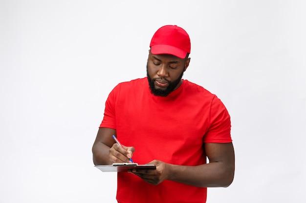 Servicio de entrega - retrato de apuesto hombre de entrega afroamericano o mensajero que muestra un formulario de documento de confirmación para firmar.