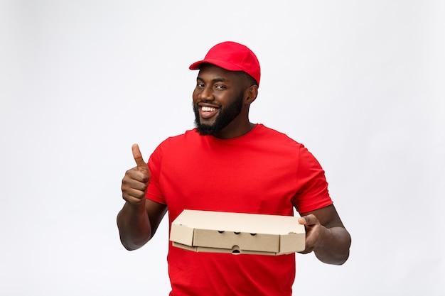 Servicio de entrega - retrato de feliz repartidor afroamericano sosteniendo un paquete de caja de pizza y mostrando los pulgares para arriba.