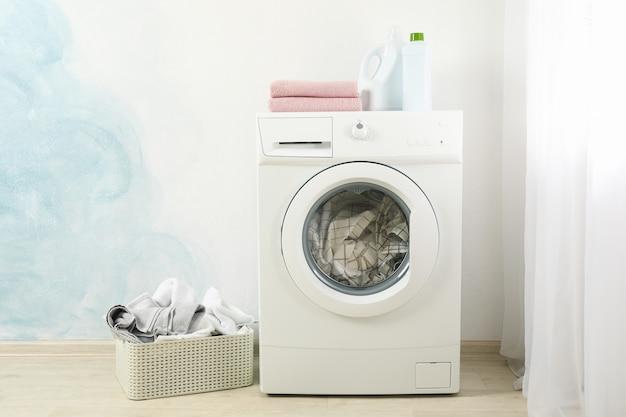 Servicio de lavandería en una lavadora y en una canasta, espacio para texto