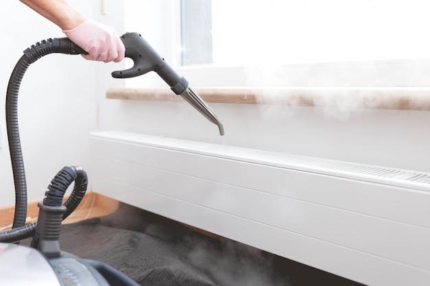 El servicio de limpieza de empleados procesa el radiador de vapor