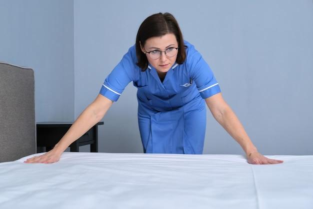 Servicio de limpieza en la habitación del hotel, mucama profesional de mujer de mediana edad preparando la habitación para hacer la cama, espacio de copia