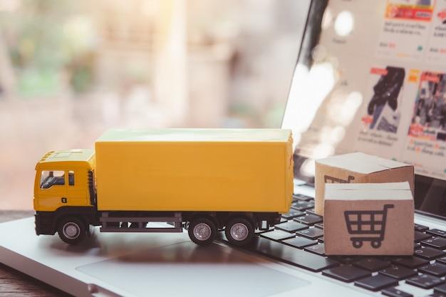 Servicio de logística y entrega: camiones y cajas de papel o paquetes con el logotipo de un carrito de compras en el teclado de una computadora portátil. servicio de compra en la web online y ofrece entrega a domicilio.