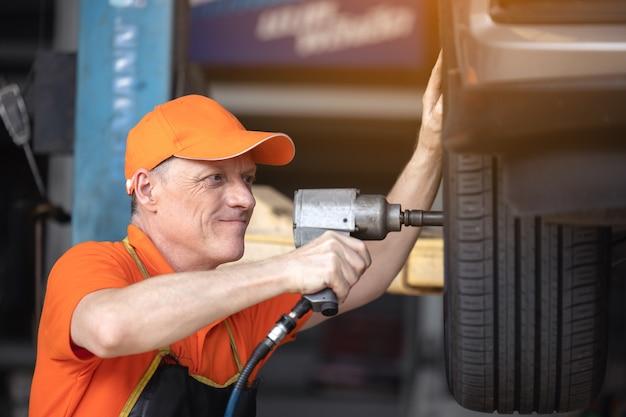 Servicio mecánico de neumáticos de coche con pistola de impacto en el garaje de la estación de servicio de reparación