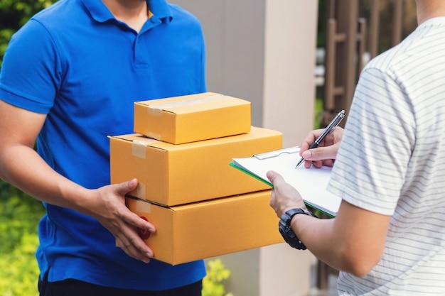 Servicio de mensajería, joven que recibe el paquete de un repartidor