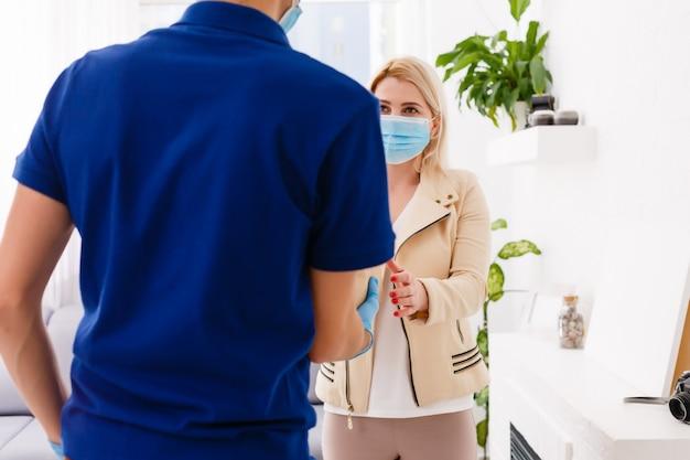 El servicio de mensajería con máscara protectora y guantes médicos entrega comida para llevar. servicio de entrega bajo cuarentena, brote de enfermedad, coronavirus covid-19