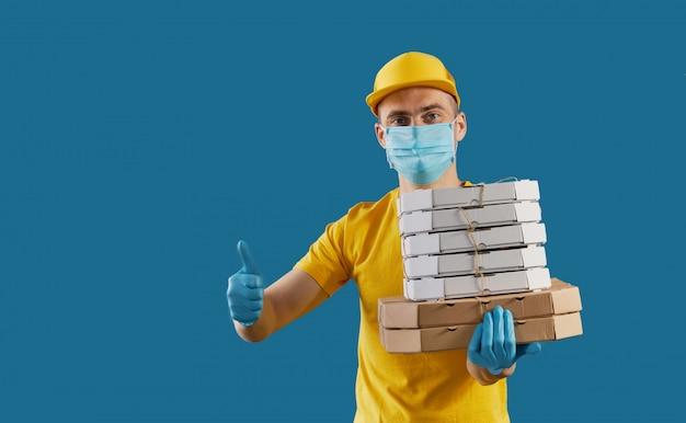 El servicio de mensajería con máscara protectora y guantes médicos ofrece comida para llevar y café. servicio de entrega en cuarentena. copiar espacio para texto