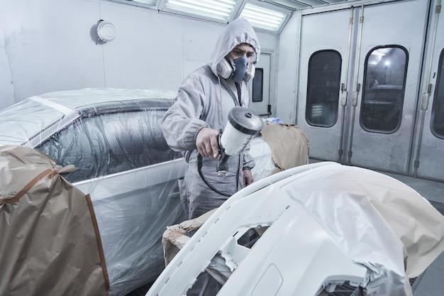 Servicio de pintura y reparación de automóviles. mecánico de automóviles en mono blanco pinta coche con pulverizador de aerógrafo en la cámara de pintura