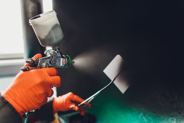 Servicio de reparación de automóviles. pintor trabajador comprobar la coincidencia de color antes de pintar. rociando líquido negro sobre la placa de montaje.