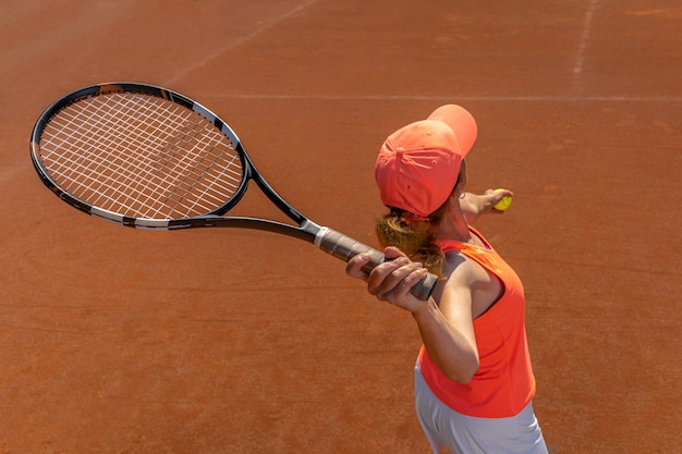Servicio de tenis de una mujer joven en la cancha.
