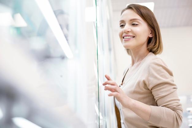 Servicios de tienda. ángulo bajo de feliz mujer alegre posando en el fondo borroso y sonriendo