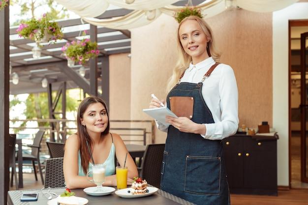 Servidor de camarera ayudando al cliente en cafe
