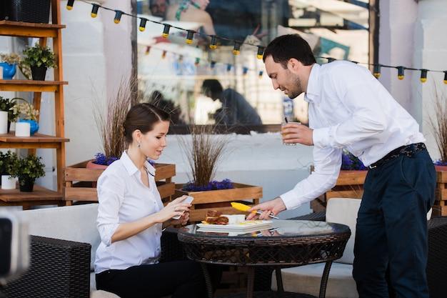 Servidor de camareros en la mesa de trabajo leyendo la lista de especialidades del menú para un grupo de personas