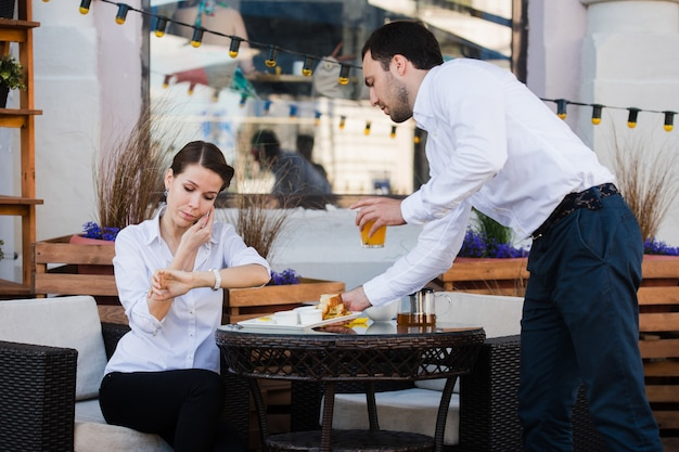 Servidor de camareros en la mesa de trabajo lista de menú de lectura especial para mujer