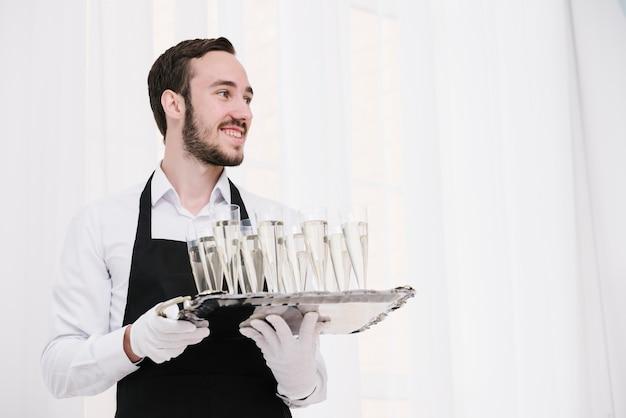 Servidor que sostiene la bandeja con copas de champán