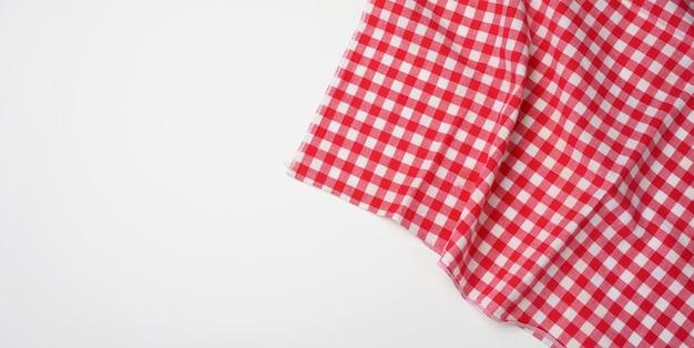 Servilleta a cuadros rojo blanco de algodón doblado sobre un fondo blanco.