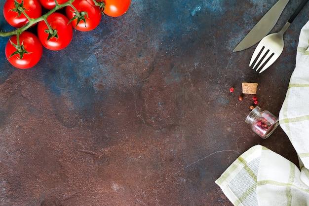Servilleta, cubiertos y tomates cherry, vista superior, copyspace