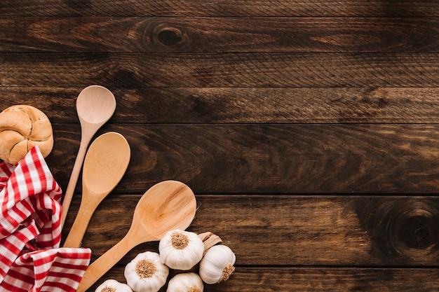 Servilleta y cucharas cerca de pan y ajo