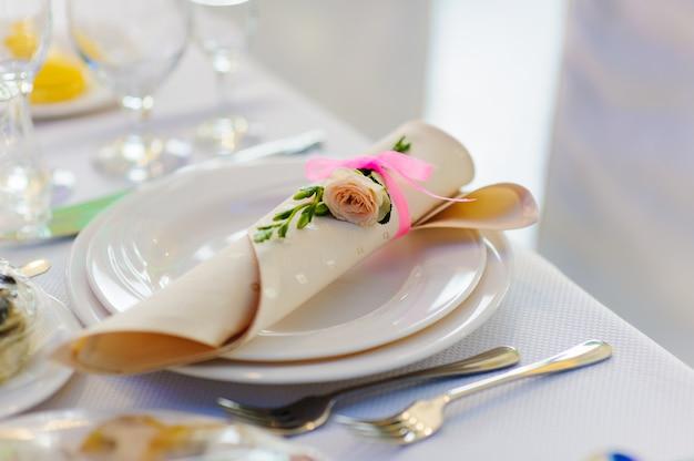 Servilleta con flor color de rosa en un plato