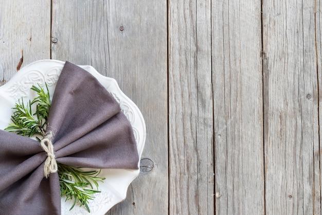 Servilleta gris en un plato con romero en vista superior de la mesa de madera con espacio de copia