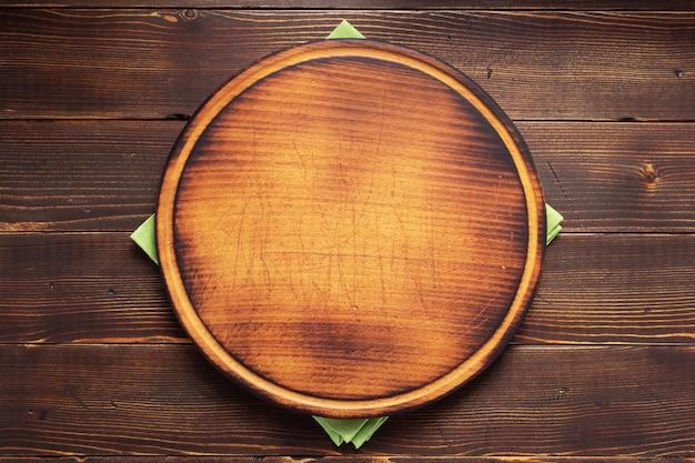 Servilleta de mantel y tabla de cortar de pizza en textura de fondo de madera