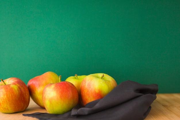 Servilleta negra con manzanas en mesa contra telón de fondo verde