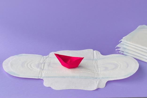 Servilleta sanitaria con el primer rojo de papel del barco en un fondo azul. ginecología. pms días críticos