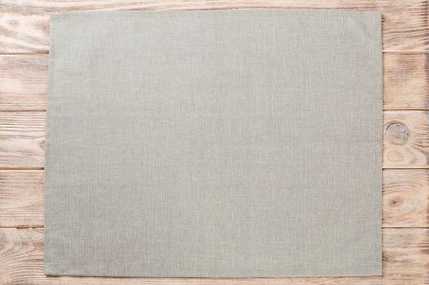 Servilleta de tela gris sobre madera rústica marrón, vista superior con espacio de copia
