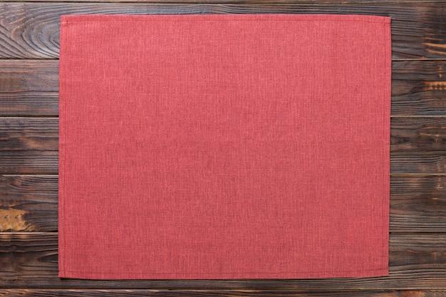 Servilleta de tela roja sobre fondo oscuro de madera rústica vista superior con espacio de copia