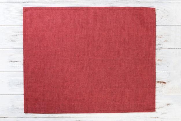 Servilleta de tela roja sobre mesa de madera rústica blanca