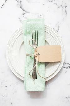 Servilleta y tenedor doblados atados con una cuerda y una etiqueta en blanco en una placa de cerámica blanca
