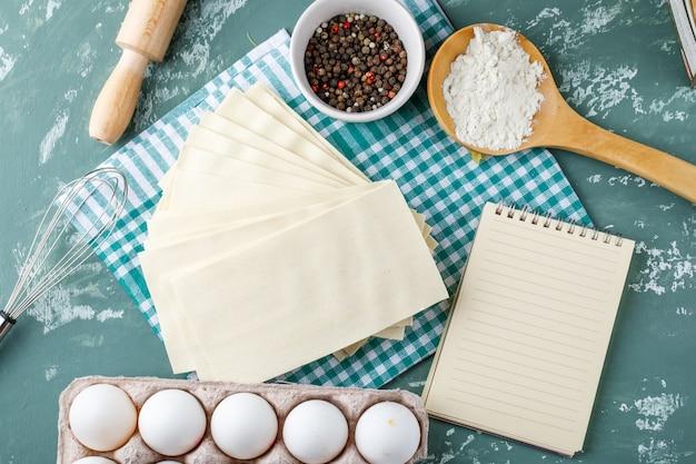 Servilletas con huevos, granos de pimienta, almidón, batidor, rodillo y cuaderno