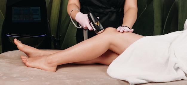 Sesión de depilación de piernas con láser utilizando aparatos modernos para una mujer joven en el centro de spa