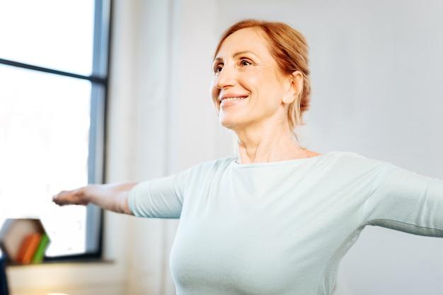 Sesión de entrenamiento por la mañana. feliz y guapa dama en forma con amplia sonrisa extendiendo sus manos durante el entrenamiento matutino