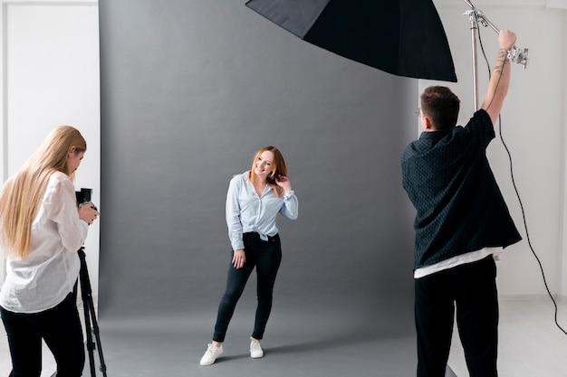 Sesión fotográfica con modelo femenina y fotógrafos.