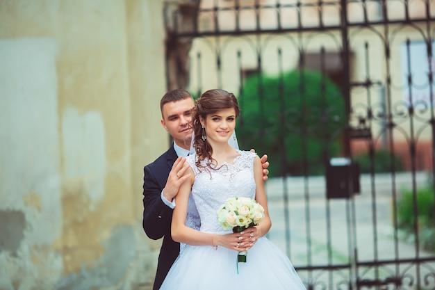 Sesión de fotos de boda. novia y el novio caminando en la ciudad. pareja casada abrazándose y mirándose.