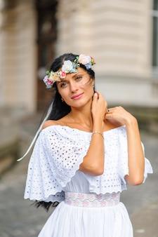 Sesión de fotos de boda. retrato de una novia encantadora en una corona sobre su cabeza. filmada en el fondo de un edificio antiguo. foto de boda de estilo rústico o boho.