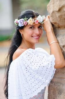 Sesión de fotos de boda. retrato de una novia encantadora en una corona sobre su cabeza. la mujer esta sonriendo. filmada en el fondo de un edificio antiguo. foto de boda de estilo rústico o boho.