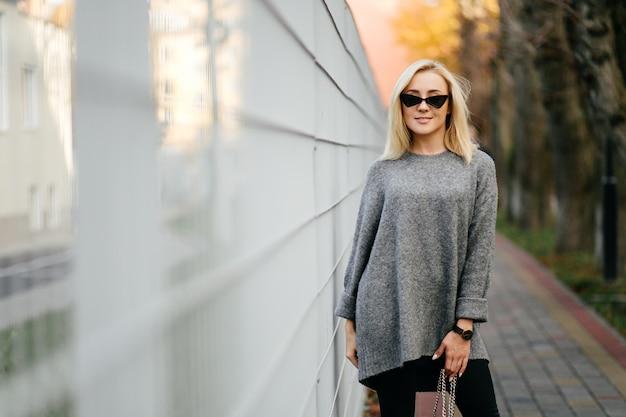 Sesión de fotos de la calle de la moda de elegante joven en una ropa gris