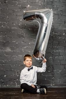 Sesión de fotos con un globo de 7 años. balón de plata con el número 7. un niño en un conjunto de fotos en el estudio.