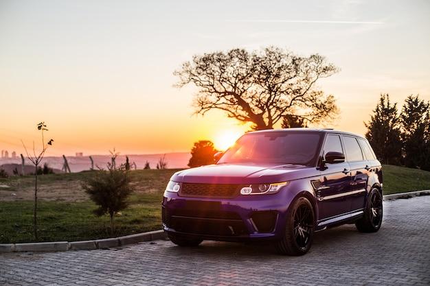 Una sesión de fotos de jeep azul en la puesta de sol.