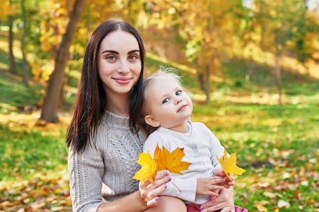 Sesión de fotos de madre con hija en el parque otoño
