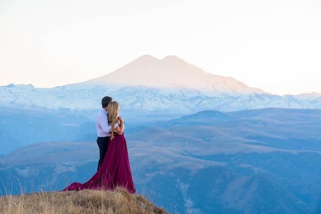 Sesión de fotos en las montañas. chica en un vestido contra las montañas. al atardecer